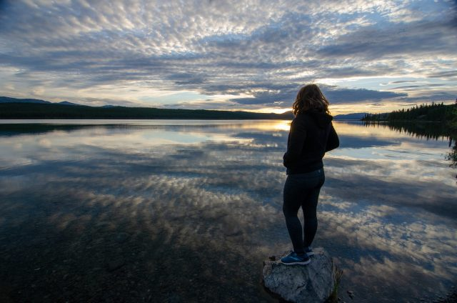 Woman looking out at a lake, as the sun is hovering just above the horizon. Planning for the sunrise and sunset are key when planning an adventure