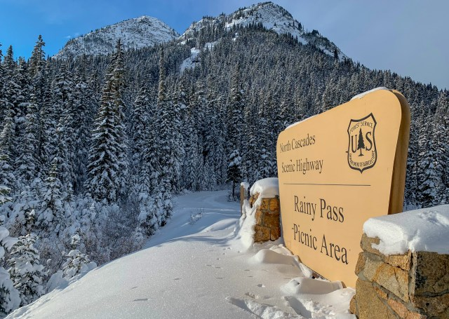 Snow covered mountains and a hiking sign that designates the Pass name