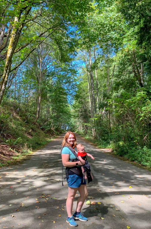 Woman carrying a baby in an infant carrier while hiking