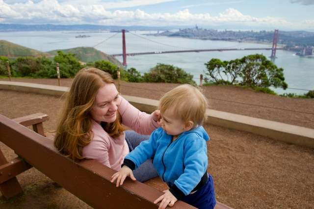 Woman with red hair dressed in pink smiling at toddler dressed in blue, with the woman sitting on a bench and the toddler standing with his hands on the back of the bench. In the background is San Francisco Bay and Golden Gate Bridge