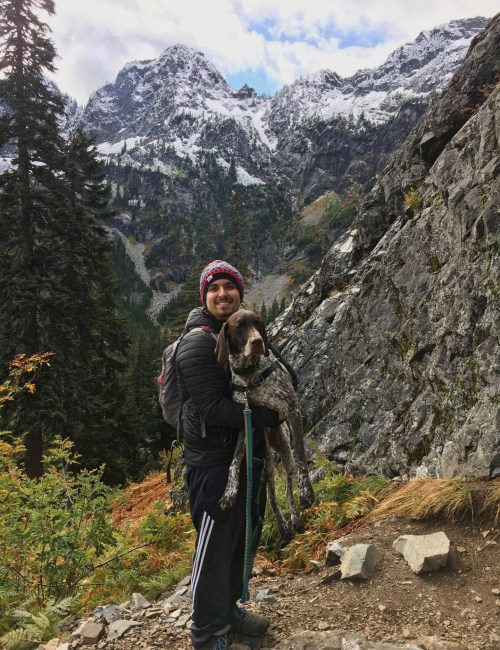 Smiling man in black jacket, multi-colored hat, holding a dog on a leash. In the background are snow covered mountain peaks and fall colored foliage.
