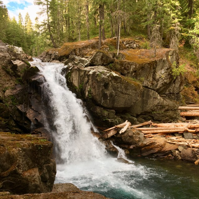 Waterfall rushing over large boulders surrounded by evergreens, falling into deep blueish green pool