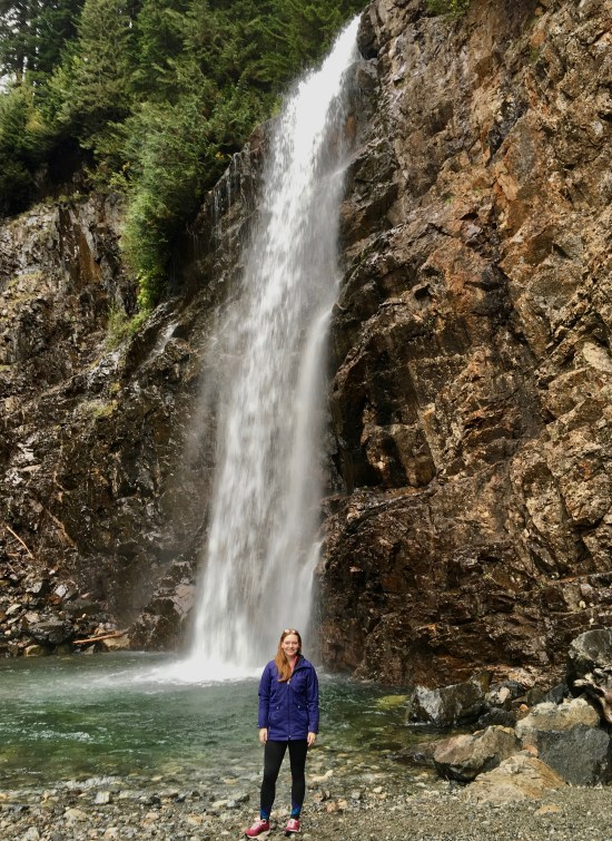 Woman in purple jacket with red hair and glasses on her head, standing at the foot of a fast-moving tall waterfall tumbling down a rock face