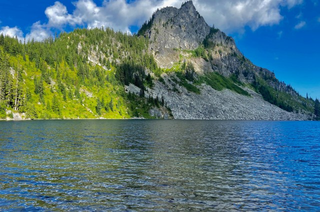 Mountain peak across from a lake, half covered in evergreens and half barren