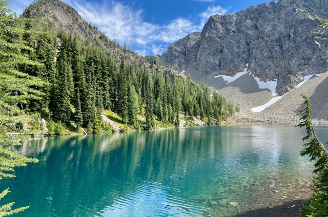 Beautiful, clear blue lake surrounded by mountains. One side is filled with evergreen trees and the other is rocky with some snow at the bottom