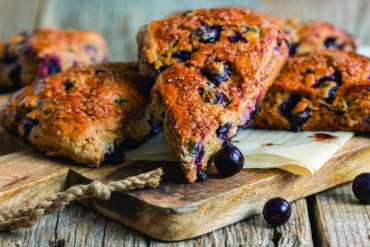Homemade scones flavored with black currants on a wooden table.