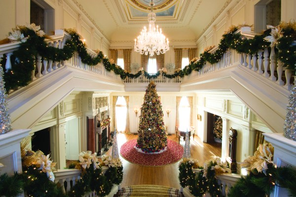 """GLANWORTH GARDENS: The Great Hall is the focal point of the house and includes a 20-foot artificial tree decorated, last year, with Christopher Radko ornaments, hand blown glass ornaments, flickering 4"""" candles tucked throughout the tree, and sprinkled with faux snow from top to bottom. The bannister combines gold-trimmed poinsettias, gold pine branches and gold mesh. The Great Hall's fireplace, one of 11 in the home, is decorated with gold pine boughs, red ornaments, gold and red ribbon, and a variety of ornaments."""