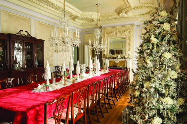 GLANWORTH GARDENS: The dining room décor corresponds with the large tree in the Great Hall. Placed upon the red poinsettia tablecloth are tapered white Christmas trees mixed with silver and white ornaments as well as white poinsettias.