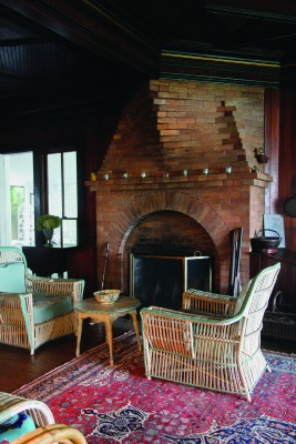 The massive brickwork fireplace creates an effect like the bow of a ship emerging from the west wall of the cozy living room.