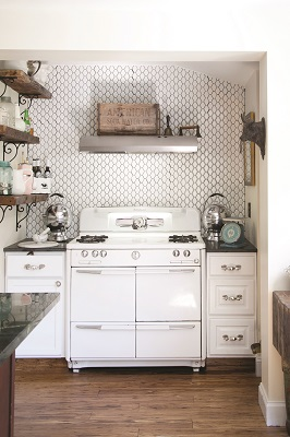 In the kitchen, a 1940s stove is set off by a contemporary backsplash and shelving made from the home's original floorboards, offering spots to display interesting finds.