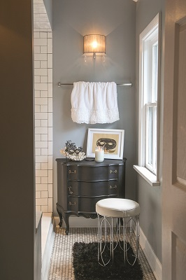 The guest bath features a quietly-classic turn with a subway tile steam shower, honeycomb floor tile, soothing blue-hued walls and original artwork by Abraham Renko.