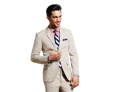 A pink and white checked shirt goes with a white and blue tie and a neutral, solid suit, a watch and a pocket square.