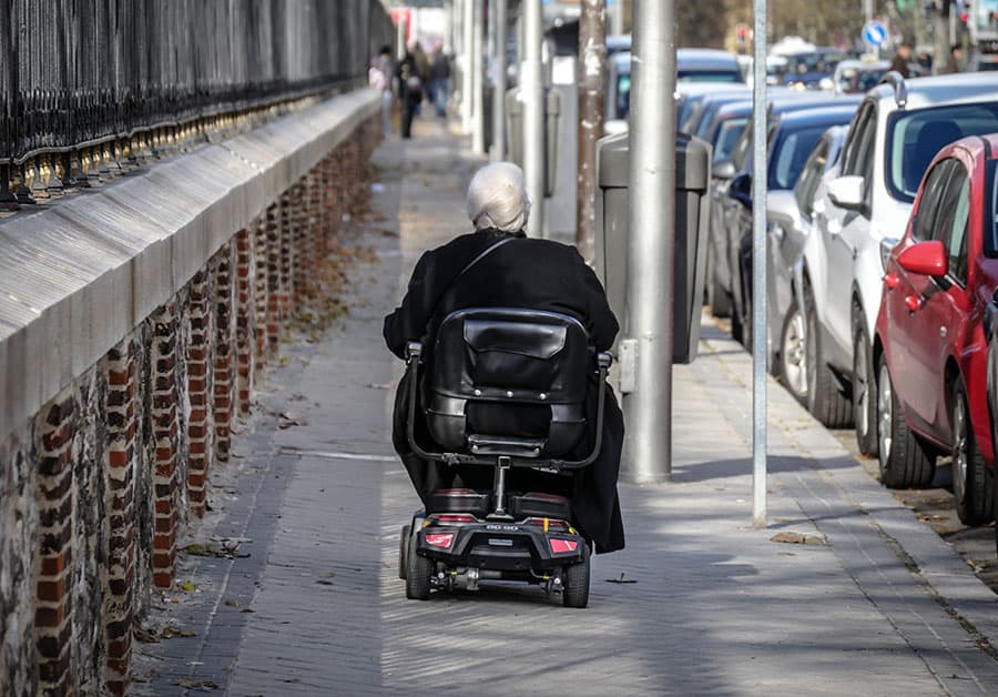 Mobility scooter user on pavement image