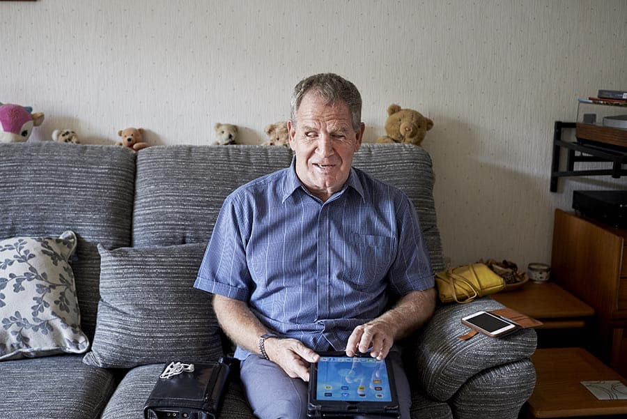 Visually impaired man using a tablet device at home image