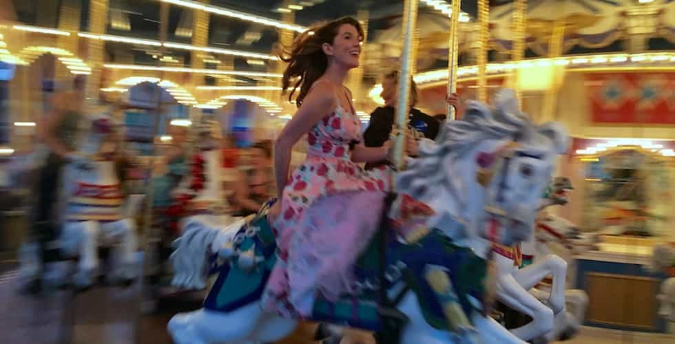 A dressed-up guest rides the carousel at Magic Kingdom during Dapper Day in 2016.