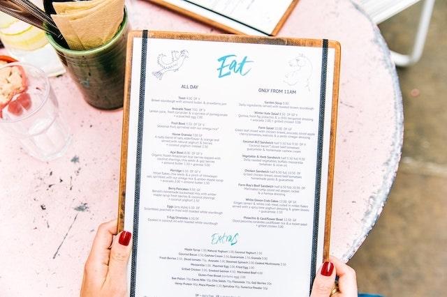Close-up of a person reading a food menu