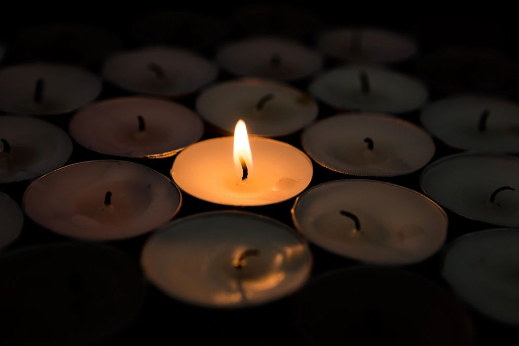 a single lit tealight candle issurrounded by unlit tealight candles