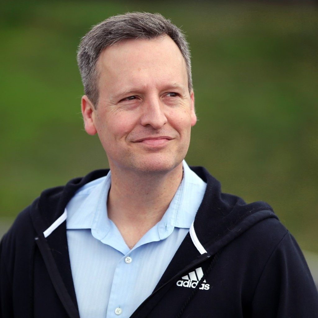Photo of King County Councilmember Dave Upthegrove wearing a dark navy adidas hoodie and light blue button up shirt.