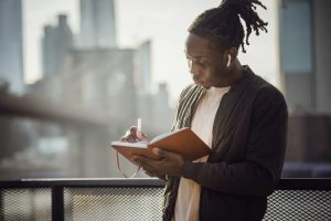 A twenty something Black male with dreads pulled into a high pony tail stands on a balcony writing in a tan journal. White air pods rest in his ears as he writes.