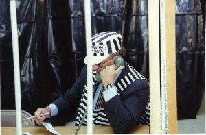 A man sits at a desk behind bars. He is ressed in a jail inmate costume. The man is on the phone looking at a piece of paper in his other hand