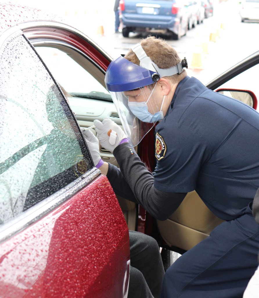 An adult male wearing a blue surgical mask, clear face shield, and dark blue EMT uniform crouches next to a red car. He's reaching him with gloved hands to an individual whose legs drape sideways out of the car. The position of his hands indicate the man is administering a shot.