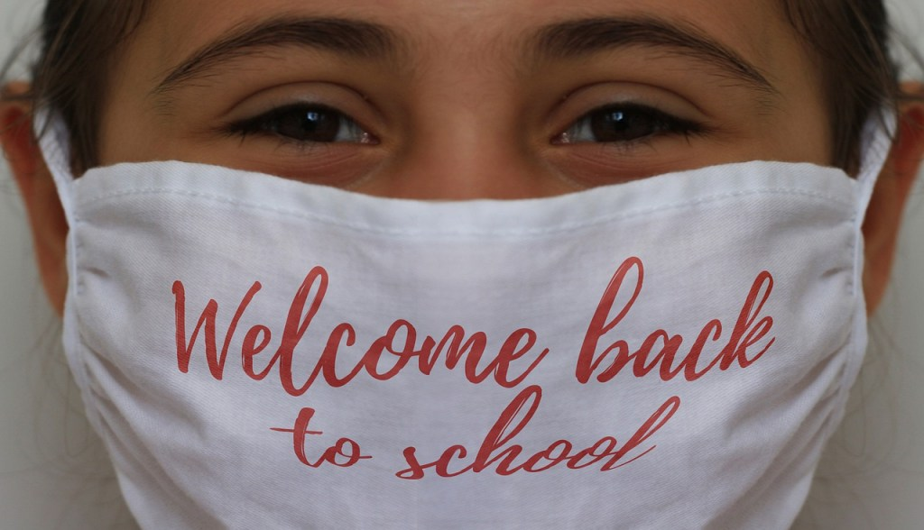 "A young girl smiles beneath a mask, her dark brown eyes and wisps of her dark hair the only parts of her face we see. Her white mask has ""Welcome back to school"" written on it in red loopy letters."