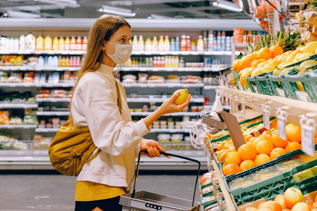 woman-in-yellow-tshirt-and-beige-jacket-holding-a-fruit in a grocery store