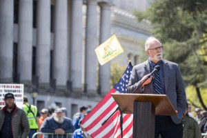State Sen. Phil Fortunato stands at a podium holding a microphone, speaking. Behind him is a crowd waving flags including the American flag and the Don't Tread om Me Flag. The rally is held at the State Capitol.