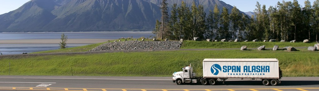 A Span Alaska tractor trailer drives on a high way with a serene mountainscape and lake background