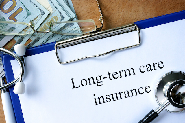 "A clipboard with ""Long-term care insurance"" written on a paper clipped on it, a stethoscope resting toward the bottom. A stack of 100 dollar bills sits in the upper left-hand corner."