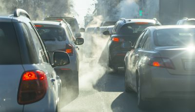cars in traffic with exhaust from their tailpipes hanging in the air