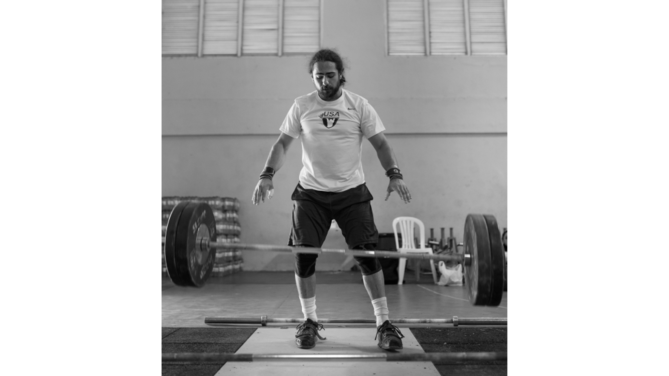 A black and white photo of Harrison Maurus, a large barbell falling to the ground in front of him.