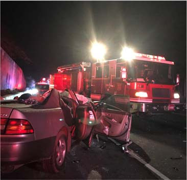 A fire engine with its lights on is parked at an angle on the road responding to a car accident. In the forefront of the photo is a crumpled sedan.