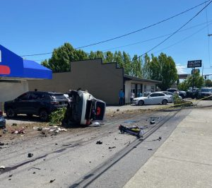 A white sedan rests on its side after a roll over Collison