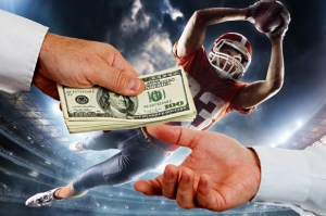 a football player jumps to catch a ball, in front of him two people exchange a stack of money.
