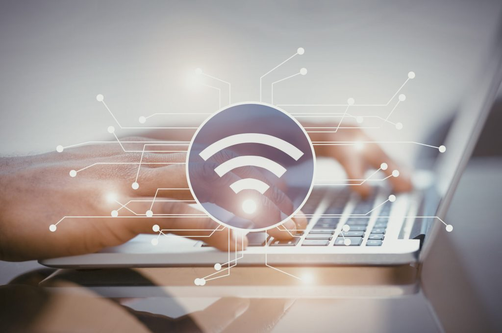 Smart contacts concept. Illustration of wifi icon with electronic connections, woman's hands using laptop on background.