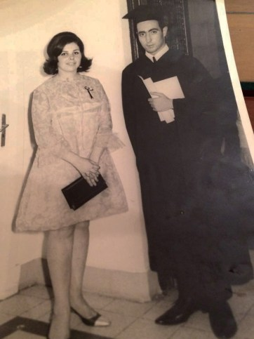 A young couple stands smiling at the camera in black and white. The man is in a graduation cap and gown, the woman in a nice dress.