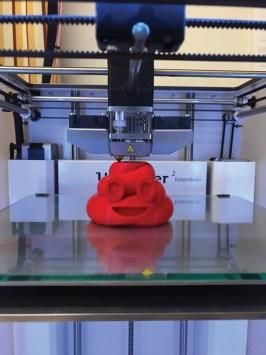 a little red smiling poop emoji being 3D printed