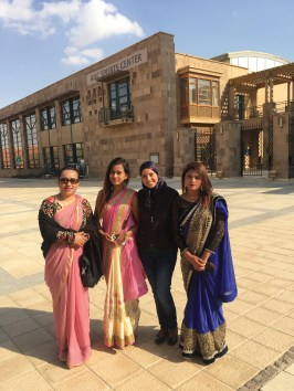 Three women in saris with a woman in jeans standing in front of AUC's Sports Center building smiling