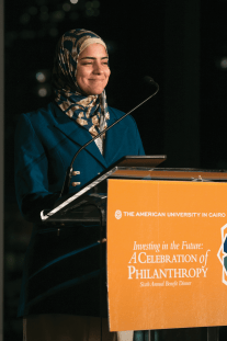 A woman in a teal and tan hijab smiles at a podium