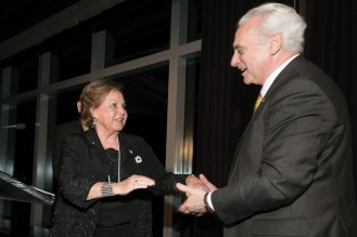 A woman in a black dress shakes hands with a man as they both smile