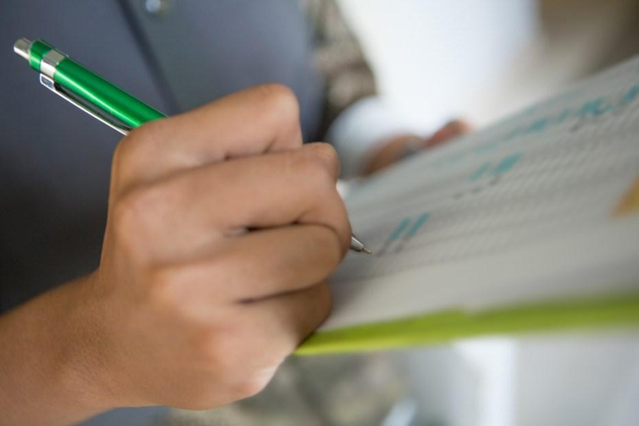 Human hand writing down on checklist, selective focus
