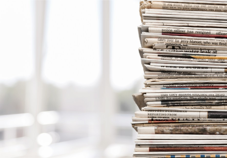 Pile of newspapers on white background