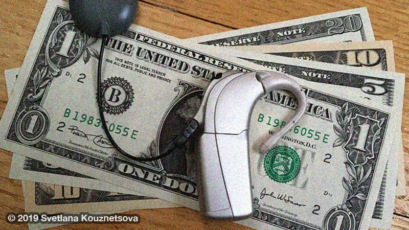 A silver cochlear implant processor on a stack of 4 cash bills - 1, 5, 10, 20 dollars.