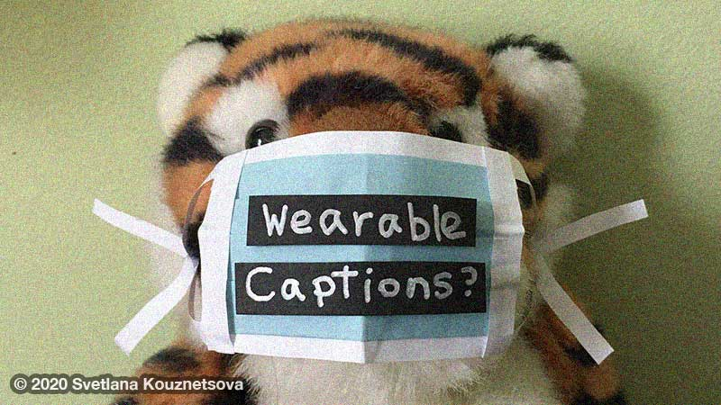 "A plushy toy tiger wearing a paper mask with words saying ""Wearable captions?"""