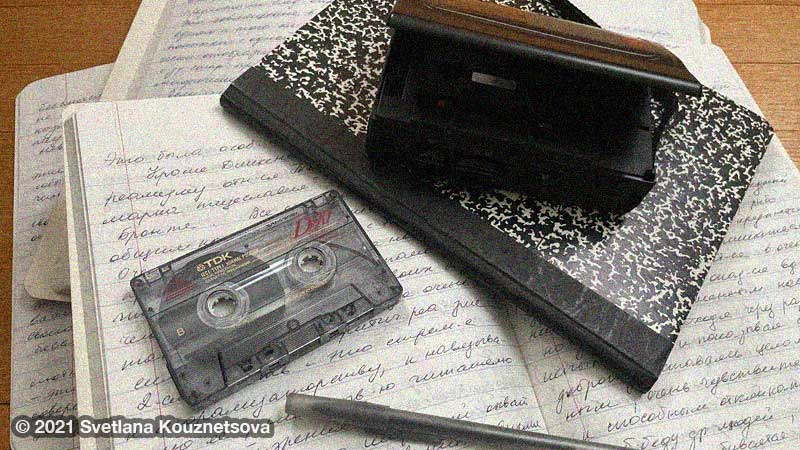 Notebooks with handwritten notes on floor. A pen, a cassette, and a tape recorder are on them.