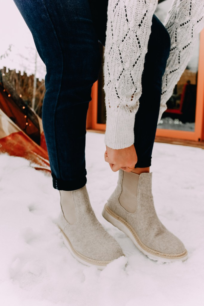 How To Cuff Women's Jeans featured by top US fashion blogger Audrey Madison Stowe; Woman standing in front of tepee wearing a sweater and jeans.
