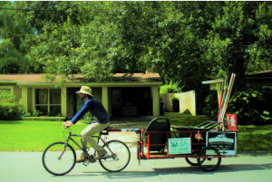 A man riding a bike with a small trailer attached with gardening tools in the back