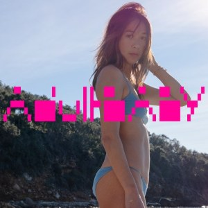 A woman in a bikini at a beach with pink lettering