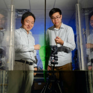 Sunny Jung, left, an associate professor of biomedical engineering and mechanics, and doctoral student Brian Chang, right, have published a new study describing how some birds dive at high speeds without injury. Their model system includes a 3-D printed replica of a gannet skull, shown here plunging into water.